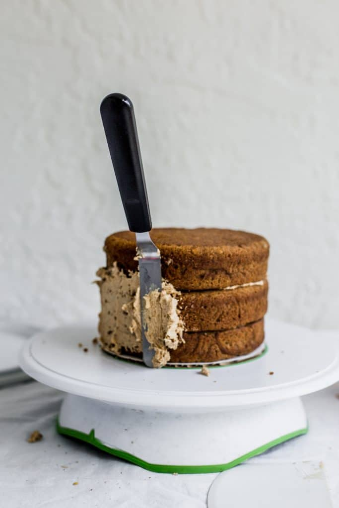 An offset spatula with frosting sticking to the side of a cake