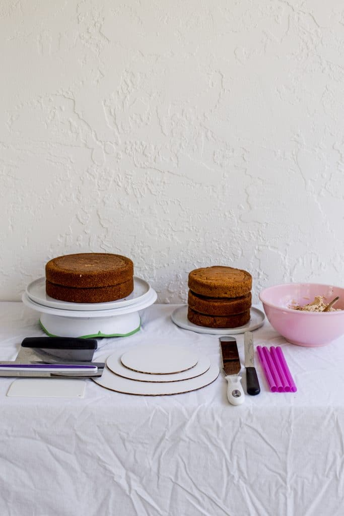 A table full of things needed to stack a cake including 2 cakes, cake boards, bench scrapers, buttercream in a pink bowl, bubble straws, a long serrated knife, and an offset spatula