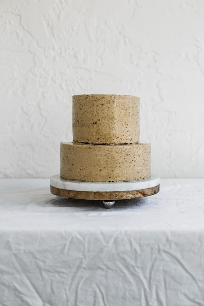 a two tier stacked beige cake sitting on a marble and wood cake plate