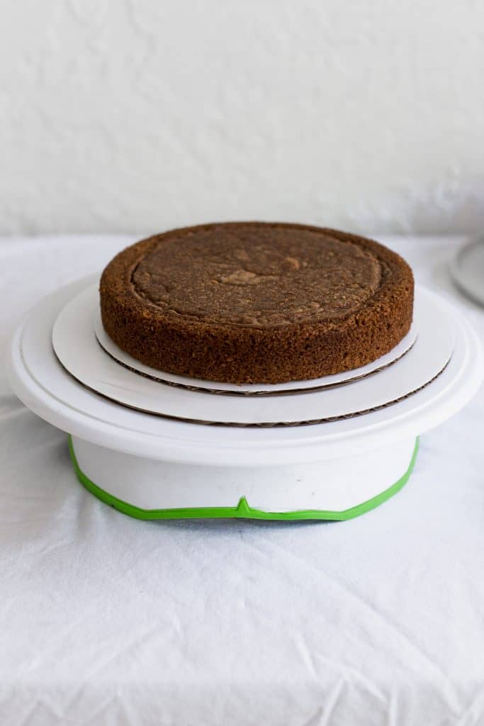 A cake sitting on 2 different size white cake boards on a cake turn table