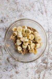 Chopped ripe bananas in a glass bowl on top of a butter sugar mixture.
