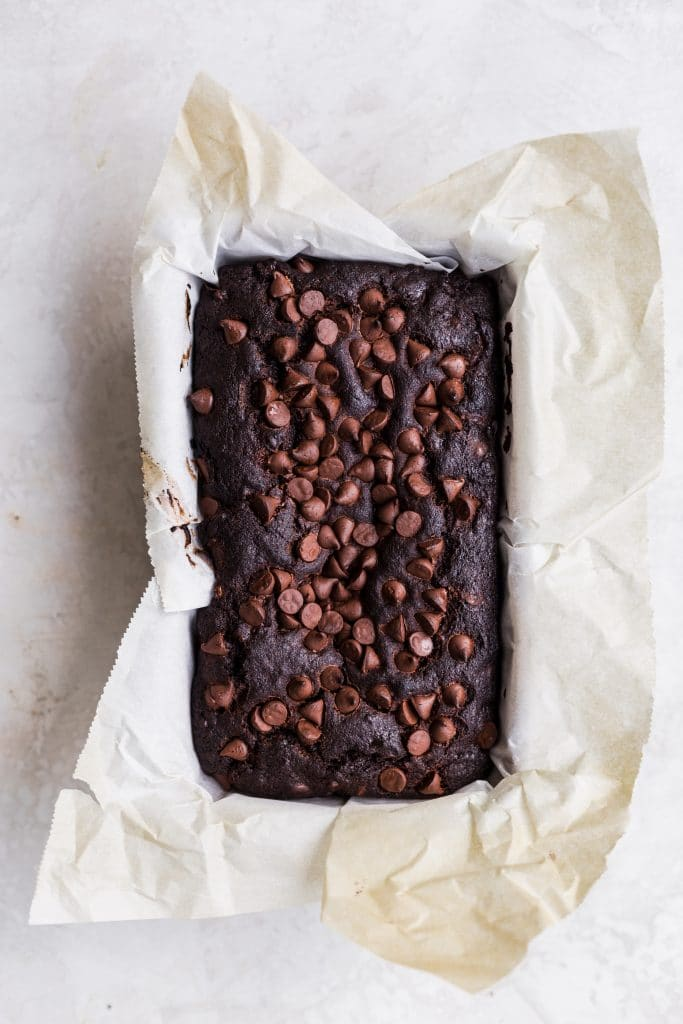 Chocolate cake with chocolate chips baked in a loaf pan lined with parchment paper.