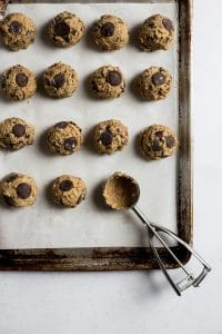 A sheet pan lined with parchment paper with balls of cookie dough lined up on it and an ice cream scooper on the side of the pan.