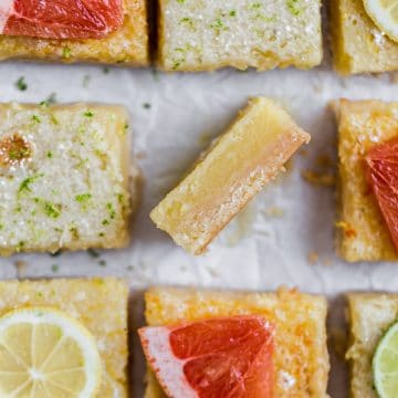 A lemon bard on its side showing the texture next to other cut squares of lemon bars topped with slices of grapefruit and lemons