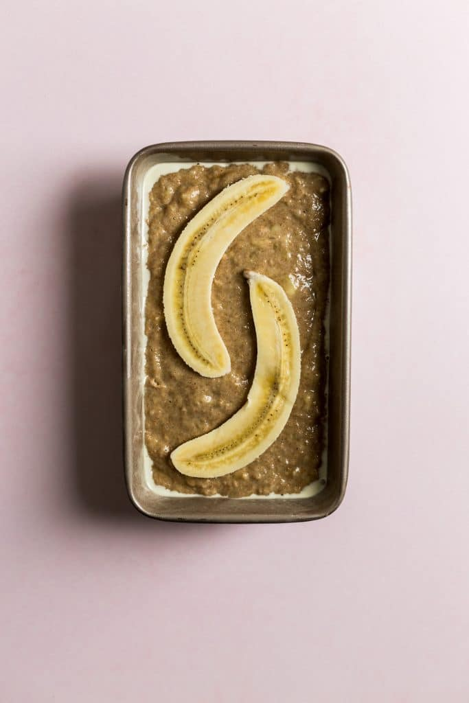 Banana bread batter in a loaf pan with a sliced banana on top