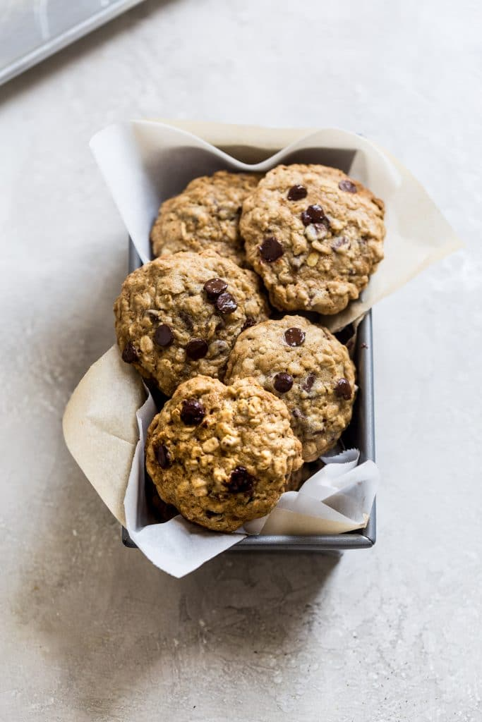 cookies sitting in a parchment paper lined loaf pan on a gray surface.
