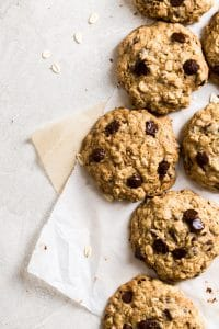 Cookies laying on two sheets on parchment paper on a gray background