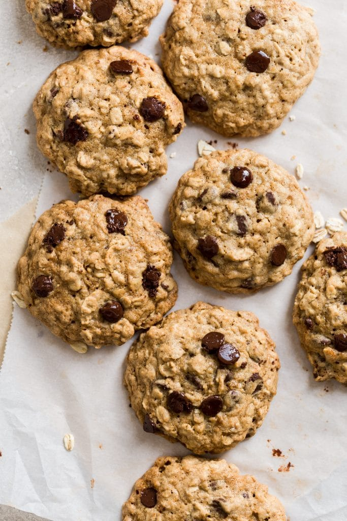 Oatmeal chocolate chip cookies laying on two sheets on parchment paper on a gray background