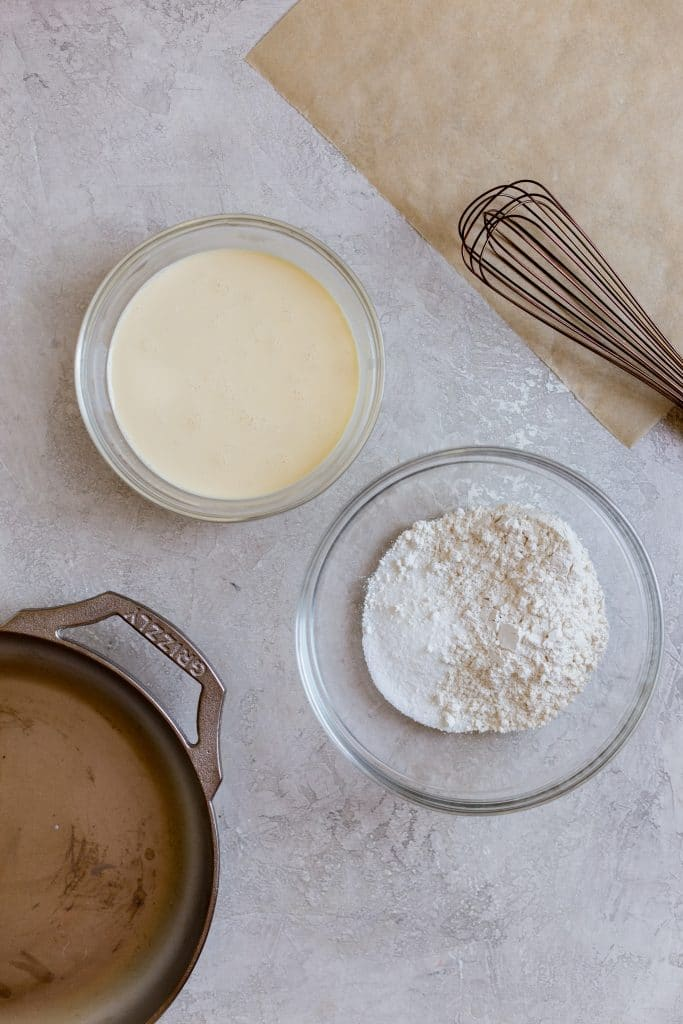 Flour in a glass bowl next to a yellow batter in another glass bowl with a cast iron pan next to it and a white whisk on the side on top of a grey surface.