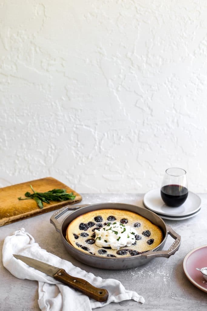 The side view of a cherry clafoutis made in a GRIZZLY nickel plated cast iron pan set on a gray table with  a cutting board in the background and a cup of wine on some plates.
