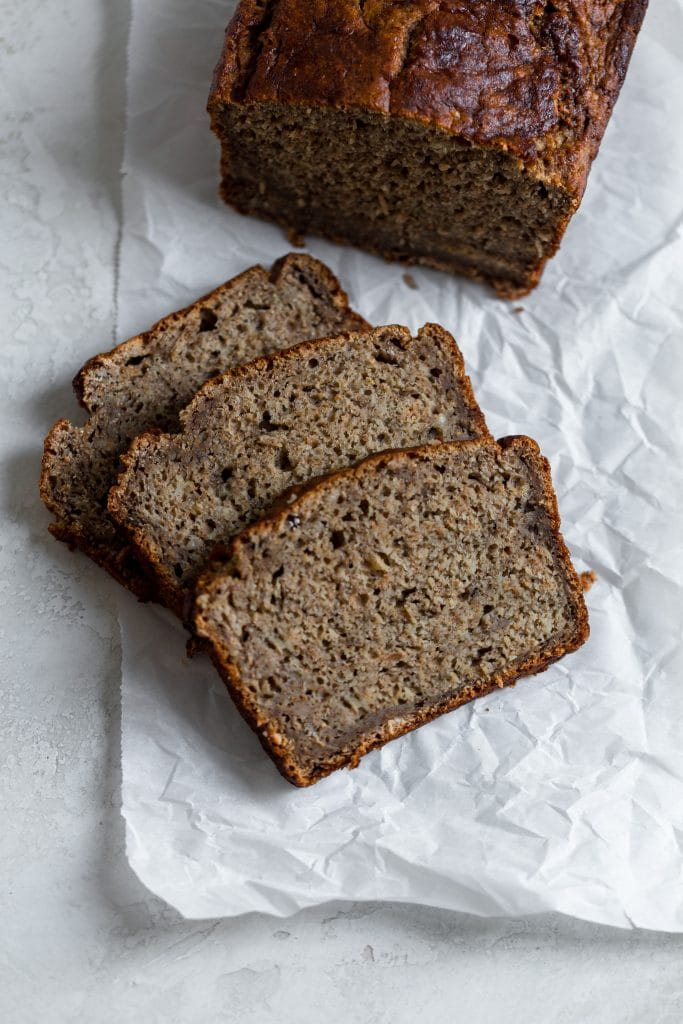Three slices of banana bread laying on parchment paper on a gray background