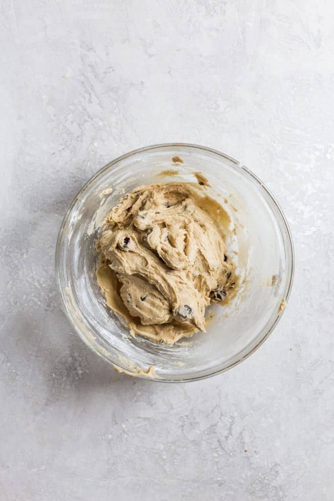 A glass bowl of chocolate chip cookie dough on a gray surface