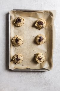 6 scoops of chocolate chip cookie dough on brown parchment paper on a small rimmed baking sheet on a gray surface