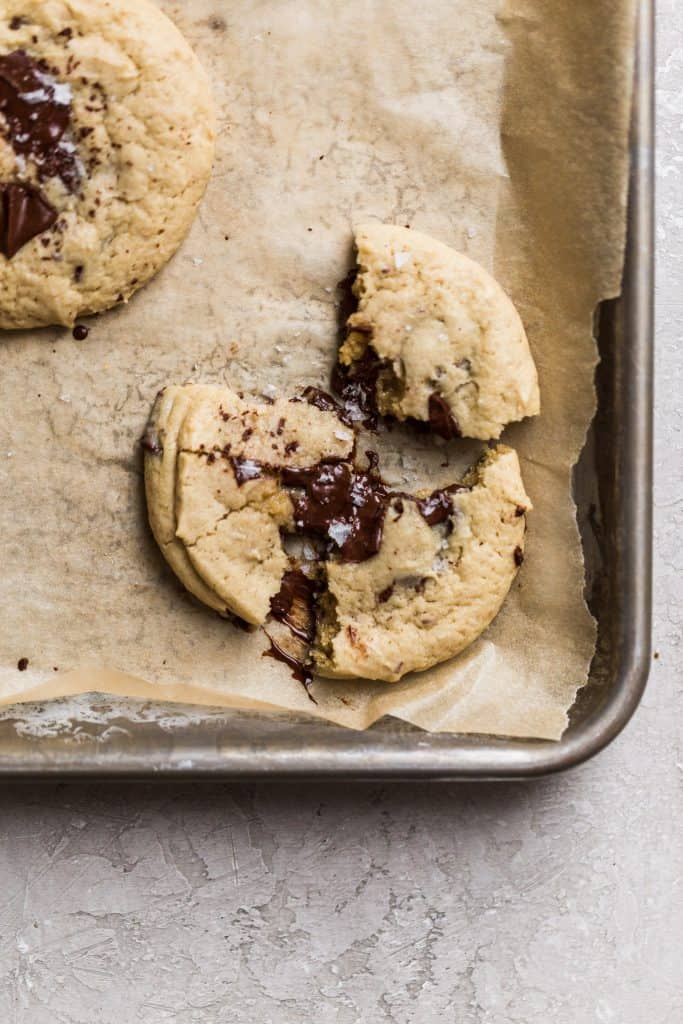 A chocolate chip cookie pulled into 3 parts with chocolate oozing out of the center on a parchment paper lined baking sheet