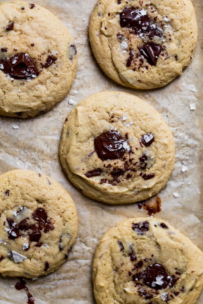 Chocolate chip cookie garnished with sea salt on brown parchment paper