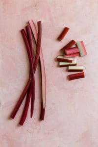fresh rhubarb in slices and chunks on a pink surface