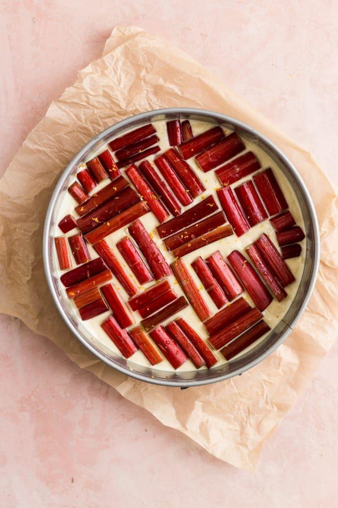 Rhubarb sliced and arranged in a herringbone shape inside oa cake pan on a pink surface
