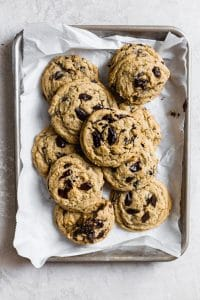 Coffee cookies piled on top of white parchment paper.