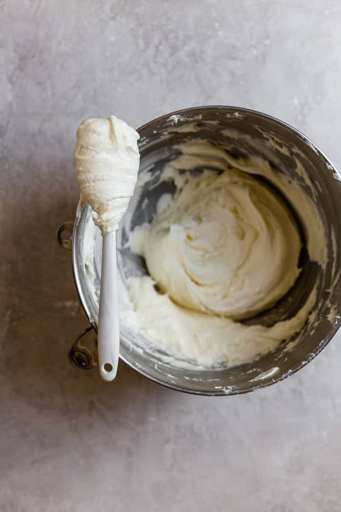 a mixing bowl filled with frosting with a spatula sitting on top of the bowl