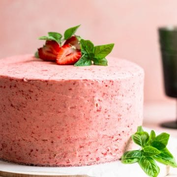 A pink frosted cake with strawberries and basil on top