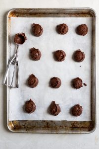 scoops of chocolate brownie cookie dough on a sheet trat