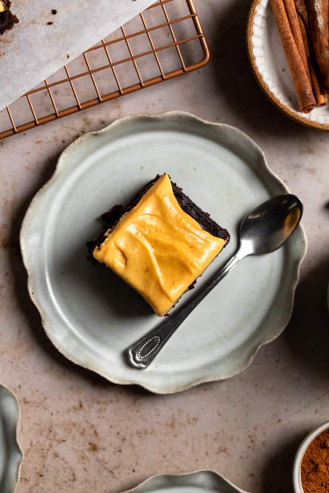 A piece of cake on a gray plate with a spoon.
