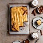 Chocolate sheet cake with pumpkin frosting on top of parchment paper and a wire rack with the corner slices cut out.