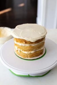 A 3 layer cake with white frosting on top.
