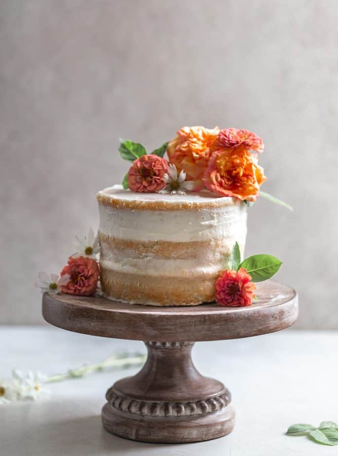 A naked cake with flowers on a wooden cake stand.
