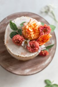 Flowers on a white cake on a wood surface