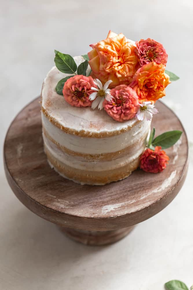 A cake topped with flowers on a wood cake stand.