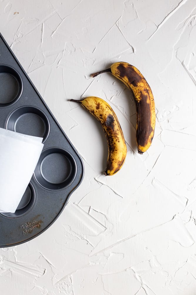Bananas with black spots on a light gray background
