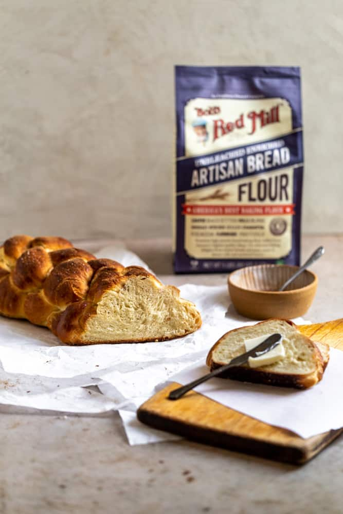 Challah braid with the end cut off on a gray surface next to a bag of flour
