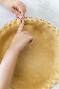 fingers crimping the edges of pie crust