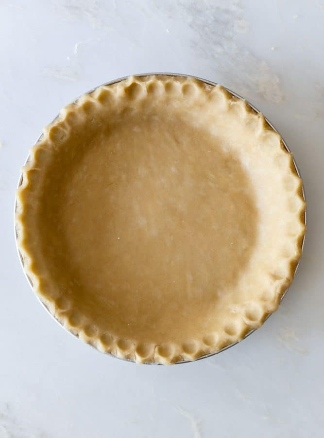 Unbaked pie crust with crimped edges on a white surface
