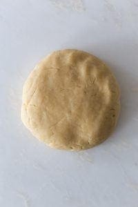 A disc of pie dough on a white surface