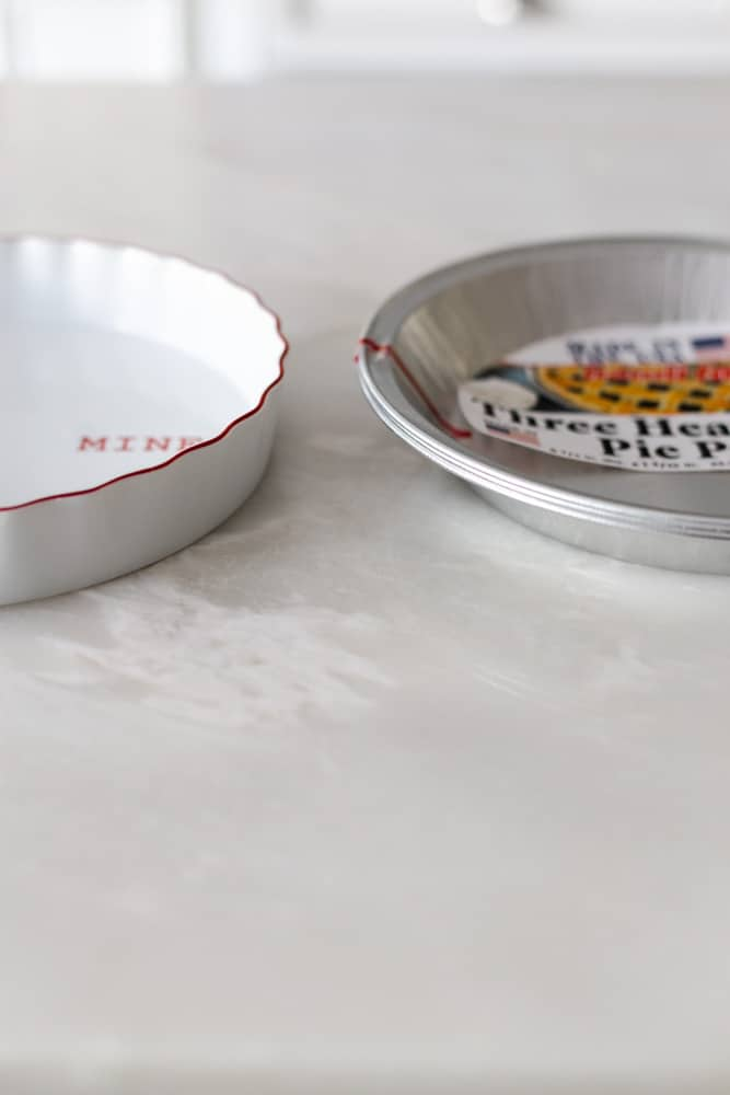 A ceramic pie plate next to an aluminum pie plate on a white surface