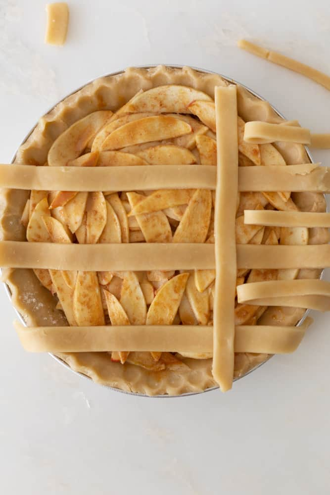 An apple pie with the beginning of a lattice crust