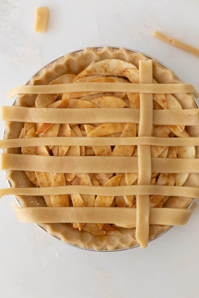 Folding over the lattice crust on apple pie