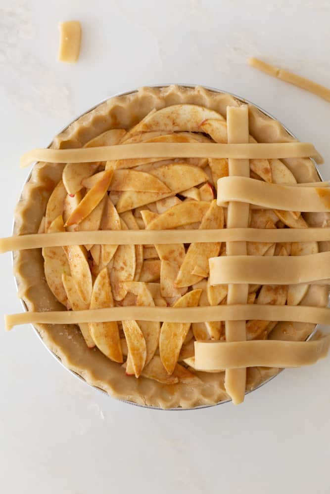 Starting the second line of a lattice crust on an apple pie
