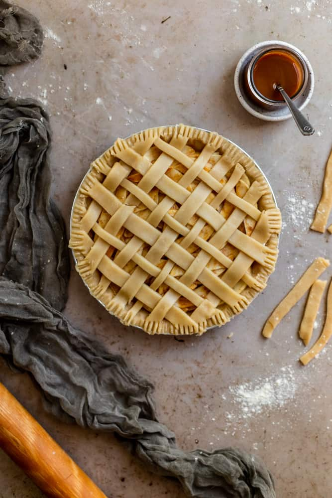 Lattice topped pie with crimped edges on a marbled brown surface