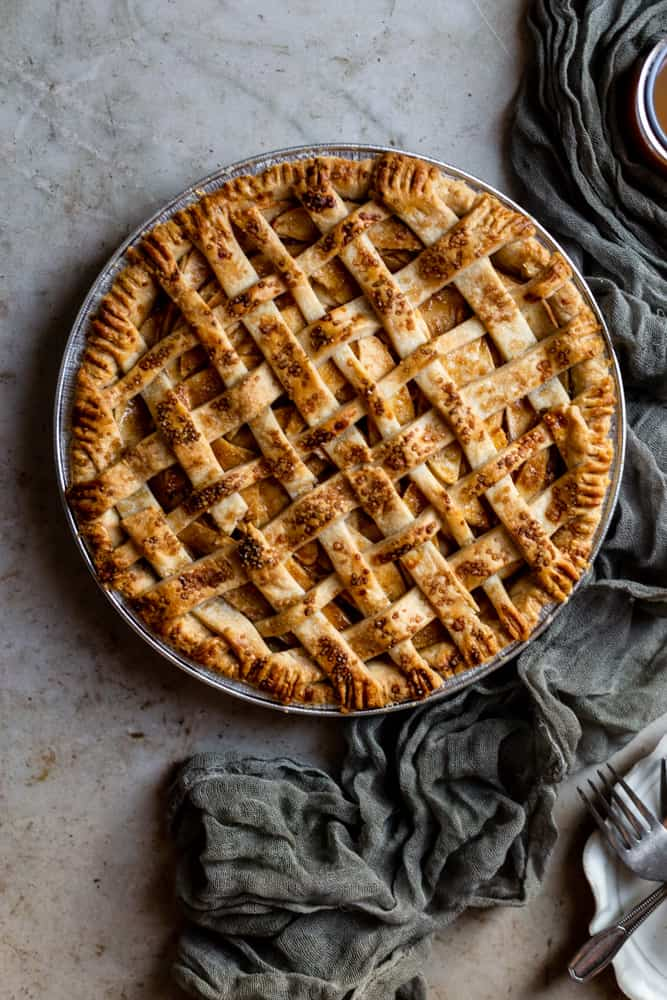 A lattice topped apple pie next to a green gauze napkin on a textured surface