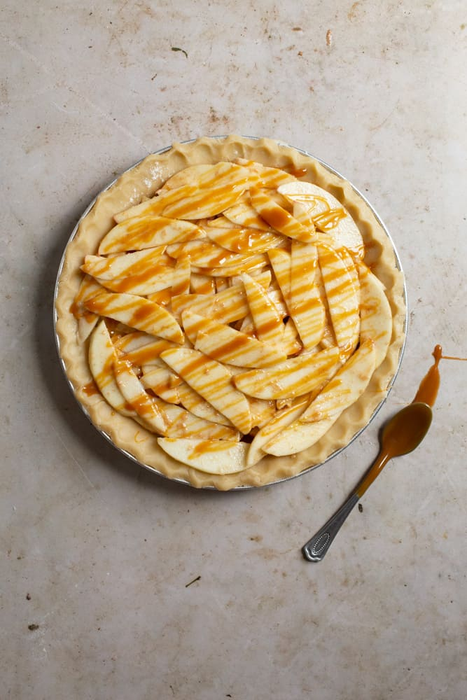 A unbaked pie crust filled to the top with sliced apples and caramel