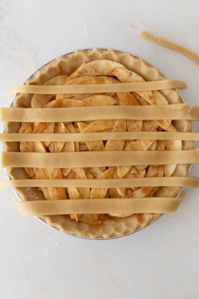 an apple pie with 6 lines of pie crust on top