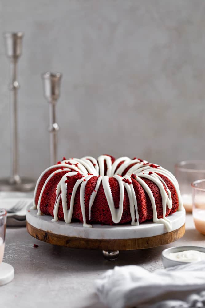 red velvet bundt cake on a marble and wood cake stand on a gray surface