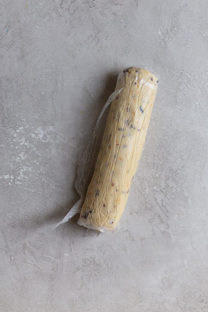 A log of cranberry orange shortbread rolled in plastic wrap