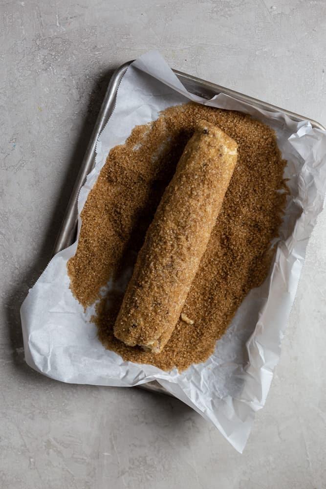 Log of cookie dough rolling in turbinado sugar in a rimmed baking sheet
