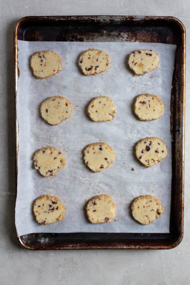 Sliced cookies on a parchment lined baking sheet