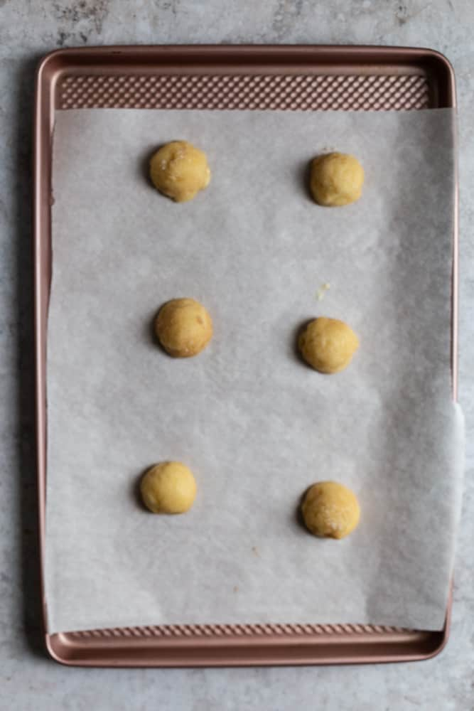 6 cookie dough balls lined on a piece of parchment paper ona cookie sheet