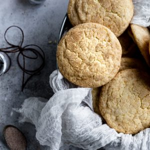 Eggnog snickerdoodles in a tray lined with cheesecloth on a textured background